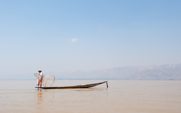 A fisherman of the Intha tribe leg-rowing in the Inle Lake